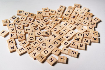 Alphabet letters on wooden scrabble pieces scattered