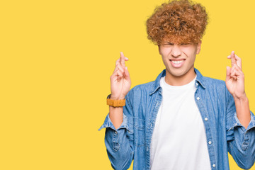 Young handsome man with afro hair wearing denim jacket smiling crossing fingers with hope and eyes closed. Luck and superstitious concept.