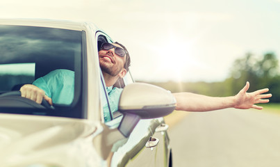 road trip, transport, travel and people concept - happy smiling man in sunglasses driving car and waving hand Wall mural