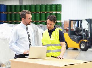 Geschäftsführer und Arbeiter bei einer Besprechung im Warenlager // Manager of a logistics company are working instruction of skilled workers