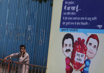 Man speaks on a phone next to a hoarding with cartoons of India's main opposition Congress Party President Rahul Gandhi and Sanjay Nirupam, President of the Mumbai Regional Congress Committee, alongside a road in Mumbai