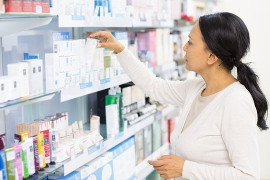 Mature Asian woman shopping pharmacy