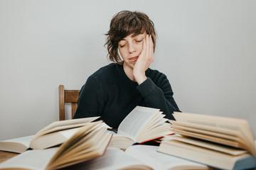 Erschöpfte Studentin sitzt am Schreibtisch vor einem Stapel Bücher