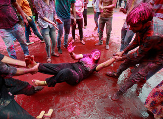A student reacts as she lies in a road while coloured powder is thrown on her during Holi celebrations at a university campus in Chandigarh