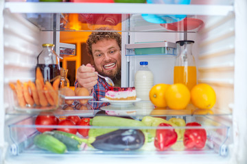 Man eating cheesecake. Unhealthy eating concept. Picture taken from the inside of fridge full of groceries.