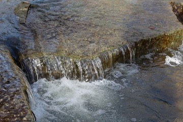 The flowing water of the brook over the rocks on a close view.
