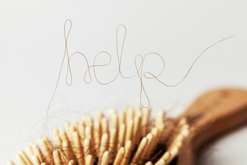 Hair loss. Comb with hair and inscriptions HELP. Concept of how to help and strengthen hair from falling out
