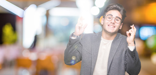 Young business man wearing glasses over isolated background smiling crossing fingers with hope and eyes closed. Luck and superstitious concept.