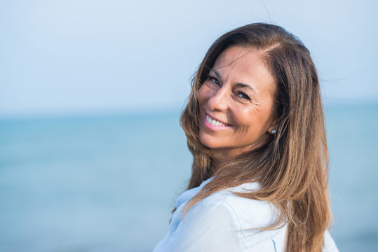 Beautiful middle age hispanic woman standing with smile on face at the ocean. Smiling confident and cheerful on a sunny day with sea view. .
