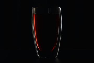 Glass full of burgundy red wine on black