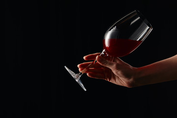 Partial view of woman holding wine glass with red wine isolated on black