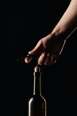 Cropped view of man opening wine bottle with corkscrew isolated on black