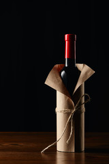 Wine bottle in paper wrapper on wooden surface isolated on black