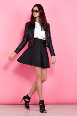 Young fashion woman in black leather jacket and black skirt. Pink background studio shot
