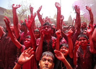 Hindu devotees raise their hands daubed in colours as they pray on a temple premises during Holi celebrations in Ahmedabad