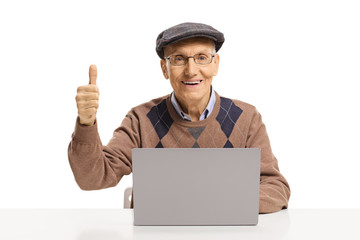 Portrait of a senior man sitting with a laptop and showing thumbs up