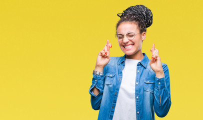 Young braided hair african american girl wearing glasses over isolated background smiling crossing fingers with hope and eyes closed. Luck and superstitious concept.