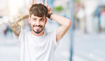Young handsome man wearing white t-shirt over isolated background Posing funny and crazy with fingers on head as bunny ears, smiling cheerful