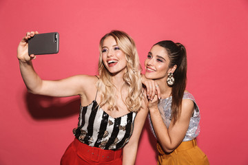 Image of two attractive girls 20s in stylish outfit holding smartphone and taking selfie photo