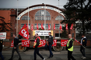 Protesters hold French workers' union CGT flags during a demonstration against the closure of sugar refineries in front of the Saint-Louis sugar beet processing plant operated by Suedzucker Group in Eppeville