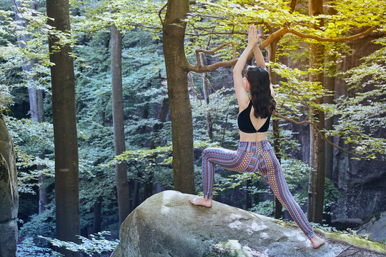 Young girl in mountains doing yoga exercise outdoor.