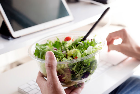 young man eating a salad at the office