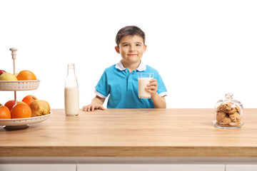 Cute little boy in a blue t-shirt holding a glass of milk behind a wooden counter