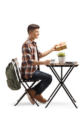 Male student holding a present and sitting in a cafe