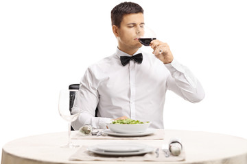 Young handsome man with a bow tie tasting red wine at a restaurant table
