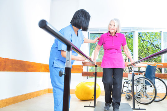 Asian nurse assisting aged senior woman training on the bars at rehab facility