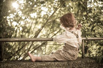 Junge mit Hosenträgerhose sitzt auf der Mauer