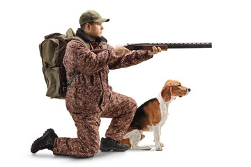Hunter kneeling with a shotgun and a beagle dog