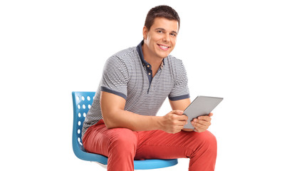 Man holding a tablet and sitting on a blue chair