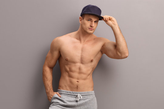 Shirtless muscular young guy posing on a gray wall