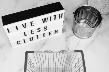 live with less clutter message on lightbox with shopping basket and trash bin