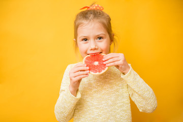 Beautiful little girl eating a round slice of grapefruit on a yellow background. . Healthy freshness concept