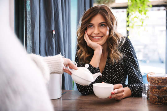 Smiling woman holding cup while barista pouring tea