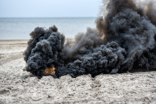 Explosion on the beach, billowing black smoke..