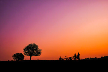 Silhouette of two trees and tourists who ride the bike at sunset at Thung Kraang, Chaiyaphum Province, Thailand