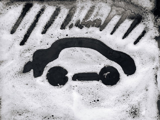 Car wash concept. The passenger car is painted on white soap suds. Black background.