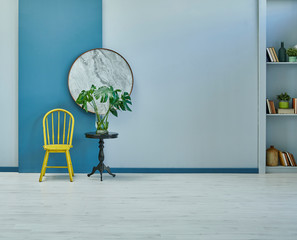 Yellow chair in the grey and blue wall background, black coffee table and vase of plant.