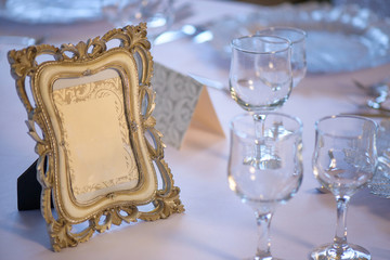 Distressed embellished wooden picture frame with copy space positioned on a table prepared for a special event, with clean drinking glasses for water and wine, decorated plates and silverware
