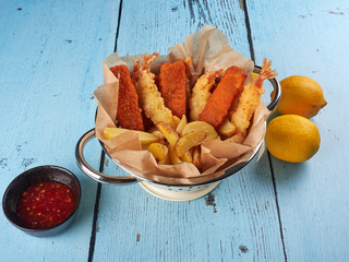 Fried fish fingers, tempura prawns and potato wedges in a colander, with lemons and sriracha sauce, on blue wooden background