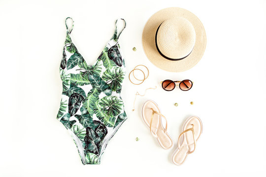 Woman's beach accessories: swimsuit with tropical print, rattan bag, straw hat on white background. Summer background. Flat lay, top view.