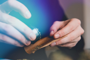 Close up marijuana joint with lighter. Man rolling a marijuana weed blunt. Man rolling marijuana cannabis blunt.
