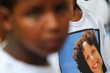 A T-shirt with an image of Maria Eduarda Alves, who was shot dead at school in 2017, is seen behind a child during a demonstration organized by the NGO Rio de Paz in memory of children killed by stray bullets, in Rio de Janeiro