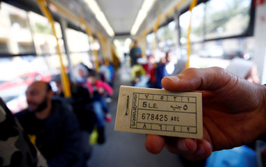 """A tram conductor shows the price of a ticket (5 Egyptian pounds) for a ride on a new tram made by Ukrainian tram manufacturer """"Tatra-Yug"""" in Alexandria"""