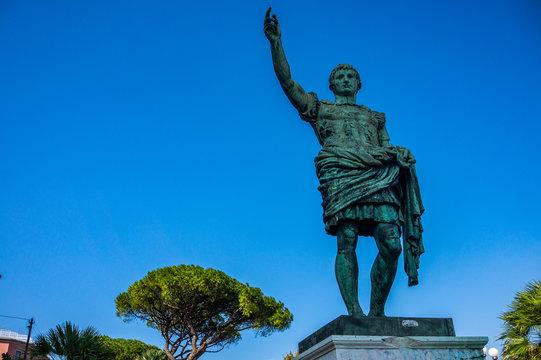 Roman emperor bronze statue on blue sky background in Naples