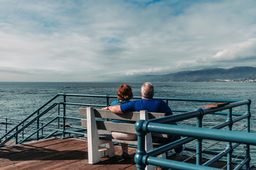 senior couple sitting on pier by the sea
