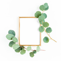 Gold frame is decorated with green branches and eucalyptus leaves on a white background. lay flat, top view